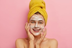 Close up portrait of happy Caucasian woman washes face with facial soap and water, wants to have healthy complexion, removes dirt and sweat sebum, yellow wrapped towel on head, isolated on pink