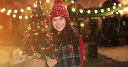 Close up portrait of happy Caucasian young woman in good mood standing on snowy street with small christmas tree, looking at camera and smiling Grateful female in decorated town at night New year mood