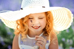 Close-up portrait of happy cute little blonde curly girl with closed eyes wearing white dress and hat and holding flower of lavender in lavender field in sunny summer day. Summer in Provence. Travel