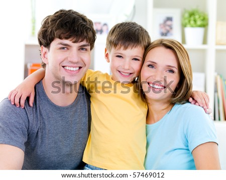 Close-up portrait of happy faces of smiling friendly young family with son