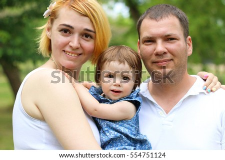 Close up portrait of happy family mother, father and little baby girl on summer green park looking at camera. Happy family outdoors. #554751124
