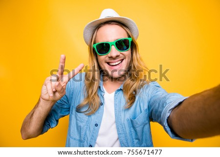 Close up portrait of happy hipster man in summer glasses with beaming smile making selfie and showing v-sign in camera standing over yellow background - Shutterstock ID 755671477
