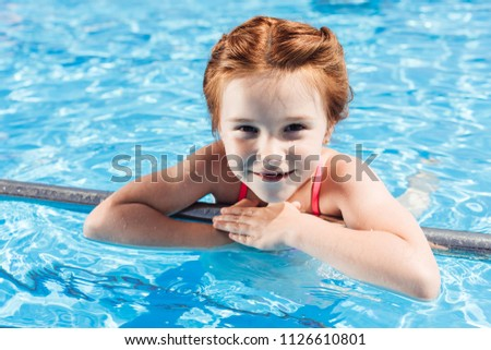 5c5ab6a6ce close-up portrait of happy little child in bikini in swimming pool looking  at camera
