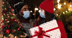 Close up portrait of happy mixed-races couple standing in evening outdoor with christmas presents and wearing medical masks in quarantine Man and woman kindly speaking on snowy street Holidays concept