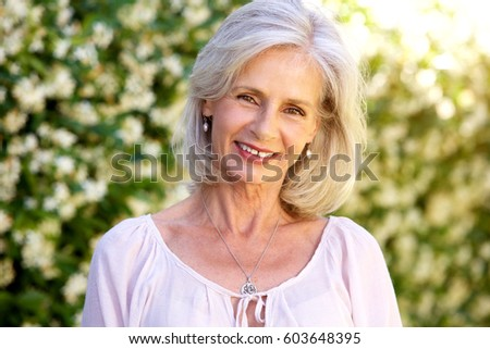 Close up portrait of happy older woman standing in garden