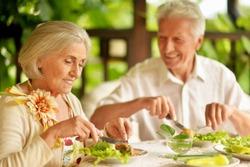 Close up portrait of happy senior couple having diner and posing on the veranda