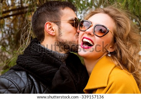 Close up portrait of happy smiling couple in love, guy kissing his girlfriend. Wearing bright outerwear, sunglasses. Outdoors lifestyle fashion portrait. Handsome brunet with beard and stunning blonde