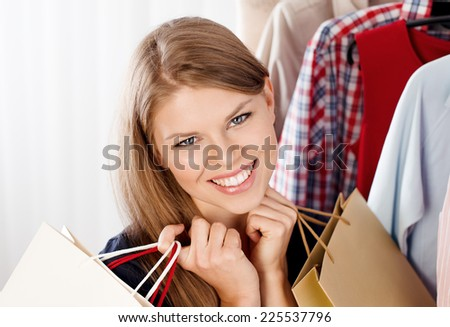 Close up portrait of happy woman buyer holding shopping bags in clothing store. Young beautiful female model happy with seasonal sales.