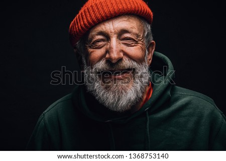 Close up portrait of happy 70-year-old optimist man with smiling wrinkled face, dressed in hipster orange hat and green hoodie, isolated over black background. Positive and cheerful at any age.