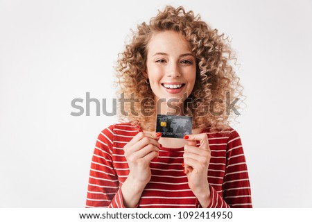 Close up portrait of happy young girl with curly hair showing credit card isolated over white background