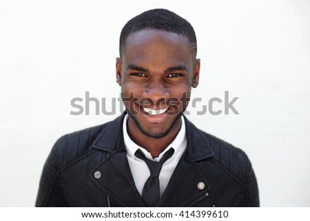 8abaa935701 Close up portrait of happy young male fashion model in leather jacket and  tie on white