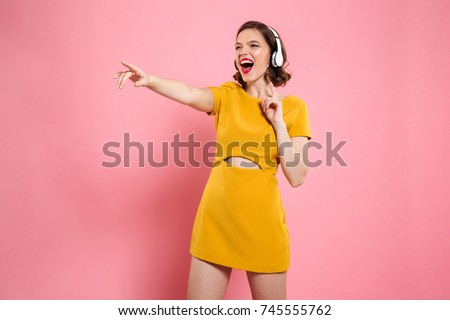 Close-up portrait of happy young woman in yellow dress and headphones pointing with finger, looking aside, isolated on pink background - Shutterstock ID 745555762