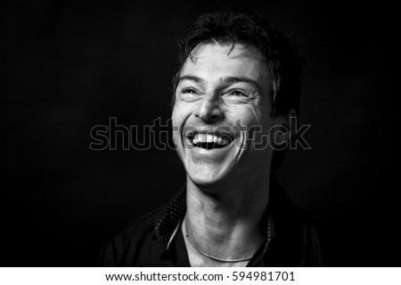 Close up portrait of hard laughing man. Isolated on black background . Monochrome picture
