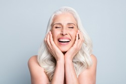 Close-up portrait of her she nice attractive excited cheerful grey-haired elderly lady touching cheeks laughing isolated gray pastel color background