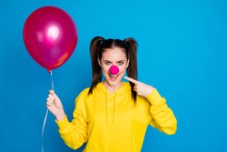 Close-up portrait of her she nice attractive funny cheerful brown-haired girl clown holding in hand air ball demonstrating pink nose isolated on bright vivid shine vibrant blue color background