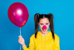 Close-up portrait of her she nice attractive funny sly cheerful cheery brown-haired girl clown holding in hand air ball laughing isolated on bright vivid shine vibrant blue color background