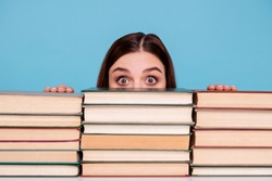 Close-up portrait of her she nice attractive intellectual smart clever brainy stunned girl hiding behind book shelf at work place station isolated over bright vivid shine blue background