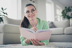 Close-up portrait of her she nice attractive lovely cute brainy dreamy cheerful cheery girl lying on floor making notes preparing annual finance plan at light white interior house living-room