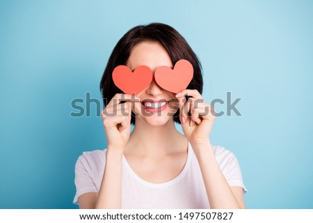 Close-up portrait of her she nice attractive lovely girlish cheerful cheery girl holding in hands two heart symbol cards closing eyes isolated on bright vivid shine vibrant blue color background