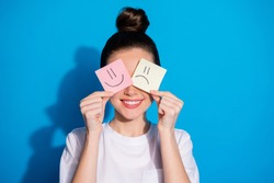 Close-up portrait of her she nice attractive pretty cheerful girl holding in hands closing eyes two different emotion stickers therapy mood isolated on bright vivid sine vibrant blue color background
