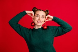 Close-up portrait of her she nice attractive pretty funky cheerful cheery girl holding in hands festive toys like earrings having fun isolated bright vivid shine vibrant red color background