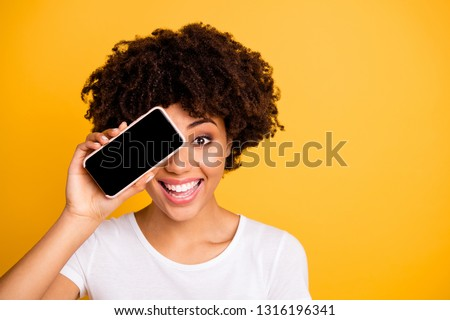 Close-up portrait of her she nice cute attractive cheerful cheery optimistic wavy-haired lady holding in hands cell hiding eye isolated on bright vivid shine yellow background