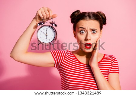 Close-up portrait of her she nice cute charming winsome lovely attractive worried girl wearing striped t-shirt holding showing clock oops omg isolated over pink pastel background