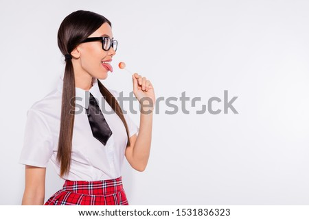 Close-up portrait of her she nice-looking attractive lovely winsome charming cool confident cheerful cheery girl wearing eyeglasses eyewear licking confectionery isolated over light white background