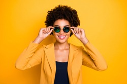 Close-up portrait of her she nice-looking fashionable attractive lovely content cheerful cheery wavy-haired girl touching specs isolated over bright vivid shine vibrant yellow color background