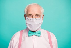 Close-up portrait of his he funky hipster elderly guy wearing gauze mask respiratory influenza flu flue grippe prevention isolated bright vivid shine vibrant teal turquoise blue grren color background