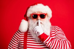 Close-up portrait of his he nice handsome mysterious white-haired Santa wearing sunglasses showing shh sign silence silent mute isolated over bright vivid shine vibrant red color background