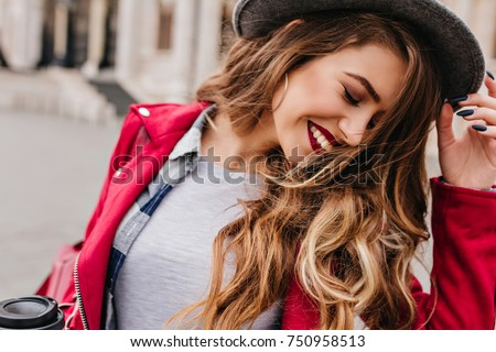Close-up portrait of inspired caucasian lady with trendy make-up spending vacation in Europe. Outdoor photo of smiling shy girl with light-brown hair walking around city in morning.