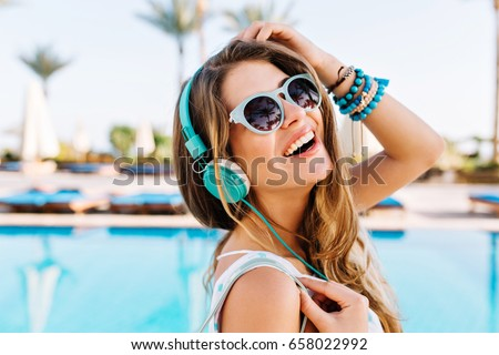 Close-up portrait of joyful laughing young lady in trendy bracelets posing with hand up near the open-air blue swimming pool. Cute girl in headphones enjoying favorite song on palm trees background