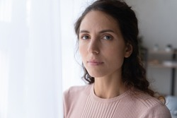 Close up portrait of joyless 30s woman standing alone near window indoor. Face of Hispanic serious female with sad eyes staring at camera. Tiredness, lack of optimism, solitude, life concerns concept