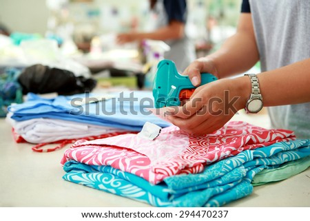 close up portrait of labeling process for cloting product at textile factory