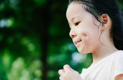 Close Up portrait of little asian girl with dimples in park