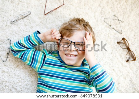 Close-up portrait of little blond kid boy with different eyeglasses on white background. Happy smiling child in casual clothes. Childhood, vision, eyewear, optician store. Boy choosing new glasses