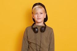 Close up portrait of little boy standing isolated over yellow background in studio, wearing black cap and dark green sweatshirt, having earphones around neck, being blond haired. Children concept.