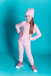 Close up portrait of little cute adorable girl in soft pink costume posing alone on blue isolated background in studio. Childhood, fashion kids, baby model concept