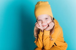 Close up portrait of little cute adorable girl in yellow costume posing alone on blue isolated background in studio. Childhood, fashion kids, baby model concept