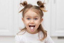 Close up portrait of little funny adorible funny child girl with pill on her tongue at home ,taking medicine, taking vitamins,tongue, eating, medical, nutrition, healthcare concept