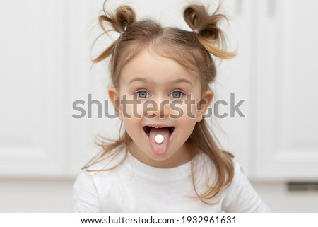 Close up portrait of little funny adorible funny child girl with pill on her tongue at home ,taking medicine, taking vitamins,tongue, eating, medical, nutrition, healthcare concept Foto stock ©