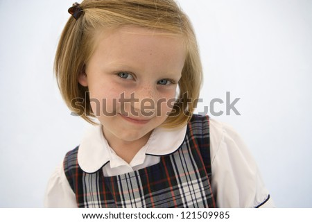 Close up portrait of little girl in school uniform smiling over white background