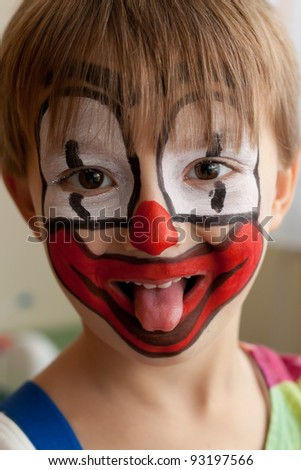 Close-up portrait of little smiling 5-years old boy dressed as a clown.