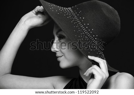 Close up portrait of lovely black dress and black hat over dark background on Beauty and Fashion theme