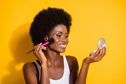 Close-up portrait of lovely cheerful wavy-haired girl applying powder on cheek looking mirror isolated on bright yellow color background