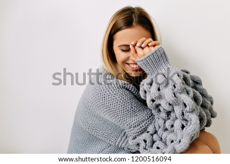 Close-up portrait of lovely happy young woman with gently smile and closed eyes holding hands near the face. Stylish girl in bright sweater having fun during photoshoot in studio.