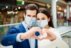 Close-up portrait of lovely her she lovely woman with his he boyfriend in suit wearing sterile mask showing heart sign together forever walk in modern mall covid19 sars outbreak protection