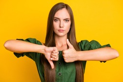 Close-up portrait of lovely serious brown-haired girl showing thumbup vs down isolated over bright yellow color background