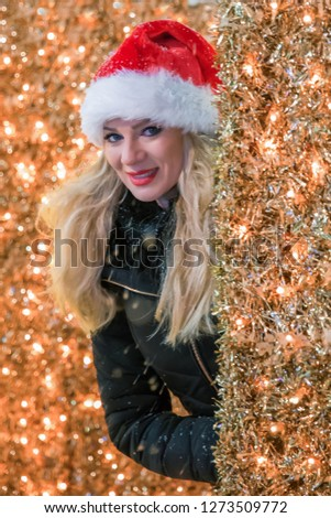 ca4de3ad41a1b Close up portrait of lovely smiling woman wearing santa claus hat and  hiding in orange Christmas